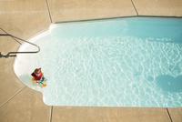 High angle view of boy playing in swimming pool 11100059930| 写真素材・ストックフォト・画像・イラスト素材|アマナイメージズ