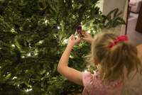High angle view of girl standing by Christmas tree at home