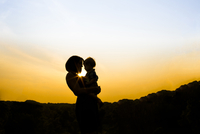 Silhouette mother carrying son while standing in park against sky during sunset 11100060054| 写真素材・ストックフォト・画像・イラスト素材|アマナイメージズ