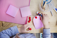 Midsection of girl making valentine greeting card at home