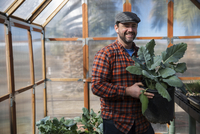 Portrait of man holding leaf vegetable plant while standing in greenhouse 11100060071| 写真素材・ストックフォト・画像・イラスト素材|アマナイメージズ