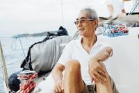 Thoughtful senior man looking away sitting in sailboat on sea 11100060080| 写真素材・ストックフォト・画像・イラスト素材|アマナイメージズ