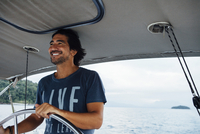 Happy man looking away while sailing boat on sea 11100060082| 写真素材・ストックフォト・画像・イラスト素材|アマナイメージズ