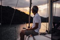 Senior man looking away while traveling sailboat on sea 11100060084| 写真素材・ストックフォト・画像・イラスト素材|アマナイメージズ
