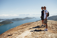 Friends looking at view while standing on mountain against sky during sunny day