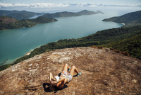 High angle view of woman relaxing on mountain by sea during sunny day