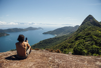 Rear view of man photographing sea while sitting on mountain against sky