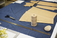 High angle view of fabric with thread spool on table at workshop
