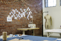 Sewing items on table against brick wall at workshop