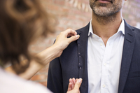 Fashion designer taking measurement on businessman at workshop