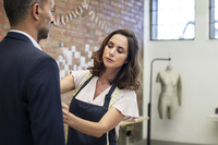 Female fashion designer taking measurement on businessman while standing at workshop