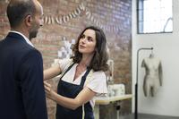 Female fashion designer talking to businessman while taking measurement at workshop 11100060119  写真素材・ストックフォト・画像・イラスト素材 アマナイメージズ