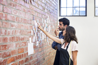 Female fashion designer showing photographs on brick wall to male colleague while working at workshop