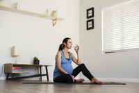 Pregnant woman drinking water while sitting on exercise mat at home