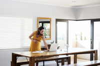 Pregnant woman using laptop computer while standing by table at home