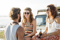 Man talking to female friends enjoying beer while sitting on off-road vehicle 11100060250| 写真素材・ストックフォト・画像・イラスト素材|アマナイメージズ
