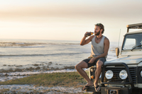 Man drinking beer while sitting on off-road vehicle at beach during sunset 11100060271| 写真素材・ストックフォト・画像・イラスト素材|アマナイメージズ