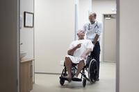 Doctor carrying patient on wheelchair in corridor 11100060343  写真素材・ストックフォト・画像・イラスト素材 アマナイメージズ