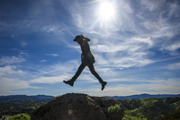 Side view of man jumping on rock formations against sky during sunny day 11100060514| 写真素材・ストックフォト・画像・イラスト素材|アマナイメージズ