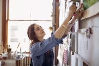 Artist hammering painting on wall in workshop 11100060528| 写真素材・ストックフォト・画像・イラスト素材|アマナイメージズ