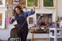 Happy female artist playing with cat in workshop 11100060534| 写真素材・ストックフォト・画像・イラスト素材|アマナイメージズ