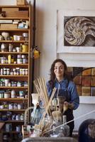 Portrait of smiling artist standing by shelf in workshop 11100060536| 写真素材・ストックフォト・画像・イラスト素材|アマナイメージズ