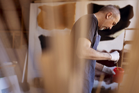 Side view of male artist mixing paint in container at workshop 11100060550| 写真素材・ストックフォト・画像・イラスト素材|アマナイメージズ