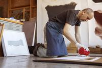 Full length of male artist making painting in workshop 11100060551| 写真素材・ストックフォト・画像・イラスト素材|アマナイメージズ