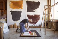 Full length of male artist making painting in workshop 11100060552| 写真素材・ストックフォト・画像・イラスト素材|アマナイメージズ