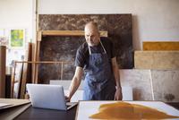 Senior artist using laptop computer by painting in workshop 11100060556| 写真素材・ストックフォト・画像・イラスト素材|アマナイメージズ