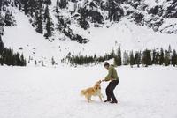 Happy man playing with Golden Retriever on snow covered field 11100060631| 写真素材・ストックフォト・画像・イラスト素材|アマナイメージズ
