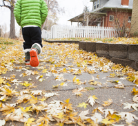 Rear view of boy running on footpath during autumn