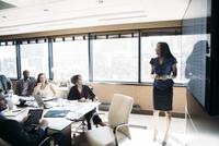 Businesswoman giving presentation in meeting at board room 11100060821| 写真素材・ストックフォト・画像・イラスト素材|アマナイメージズ