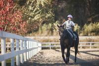 Girl horseback riding in ranch 11100060914| 写真素材・ストックフォト・画像・イラスト素材|アマナイメージズ