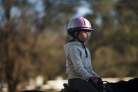 Side view of girl horseback riding in ranch 11100060921| 写真素材・ストックフォト・画像・イラスト素材|アマナイメージズ