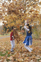 Happy siblings playing with autumn leaves in park