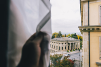 Cropped hand of man holding curtain at window against buildings 11100061067| 写真素材・ストックフォト・画像・イラスト素材|アマナイメージズ
