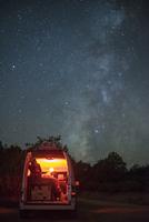 Man sitting in illuminated camper van against star field at night 11100061146| 写真素材・ストックフォト・画像・イラスト素材|アマナイメージズ