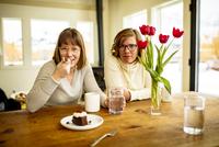 Portrait of sisters sitting at table 11100061206| 写真素材・ストックフォト・画像・イラスト素材|アマナイメージズ