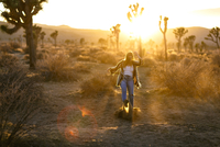Playful woman kicking sand on field at Joshua Tree National Park 11100061222| 写真素材・ストックフォト・画像・イラスト素材|アマナイメージズ