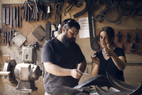 Coworkers discussing in blacksmith shop 11100061447| 写真素材・ストックフォト・画像・イラスト素材|アマナイメージズ