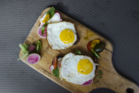 High angle view of fried eggs with bread and vegetables on serving board 11100061517| 写真素材・ストックフォト・画像・イラスト素材|アマナイメージズ