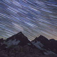 Low angle view of star trails over mountains at night 11100061566| 写真素材・ストックフォト・画像・イラスト素材|アマナイメージズ