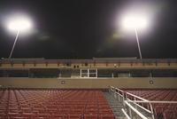 Low angle view of empty seats at illuminated American football stadium