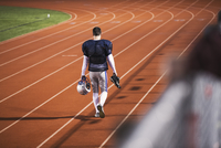 Rear view of American football player walking on sports track in stadium