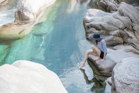 Side view of female hiker dipping foot in river while sitting on rock 11100061717| 写真素材・ストックフォト・画像・イラスト素材|アマナイメージズ