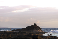 Distant view of woman standing on rock by sea against cloudy sky 11100061725  写真素材・ストックフォト・画像・イラスト素材 アマナイメージズ