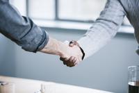 Midsection of businessmen handshaking in board room 11100061765| 写真素材・ストックフォト・画像・イラスト素材|アマナイメージズ