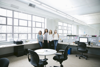 Portrait of confident businesswomen standing by desk in office 11100061856| 写真素材・ストックフォト・画像・イラスト素材|アマナイメージズ