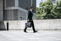 Full length side view of businessman carrying briefcase while walking on bridge in city 11100061921| 写真素材・ストックフォト・画像・イラスト素材|アマナイメージズ